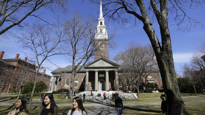 People walk on the campus of Harvard University in Cambridge, Mass. Harvard's investments in the timber industry inspired student protests in 2014.