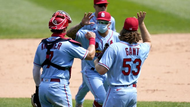 St. Louis Cardinals catcher Andrew Knizner, left, and relief pitcher John Gant fake a high-five with infielder Kolten Wong after the Cardinals' 5-1 win over the Chicago White Sox in Game 1 of a doubleheader Saturday in Chicago.