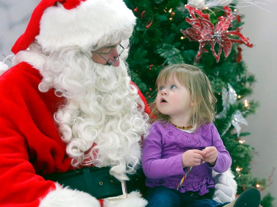 In this Saturday, Dec. 2, 2017, file photo, John Christensen talks with Zoey Martin, 2, while appearing as Santa Claus in Casper, Wyo. Christensen has portrayed Santa throughout Casper for more than two decades.