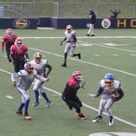 Southfield Falcons player Raymond Bryant (right) uses his speed to fly past opponents in a recent youth football league game.