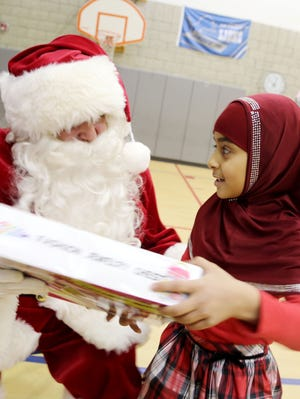 Eman Algalham, 7, receives a fashion jewelry set from Santa during a holiday party Thursday, Dec. 19, 2013, at Salina Elementary School in Dearborn, Mich.