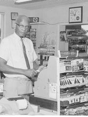 In this historical photo, Ross Evans stands behind the cash register at Evans Grocery on Florida Avenue.