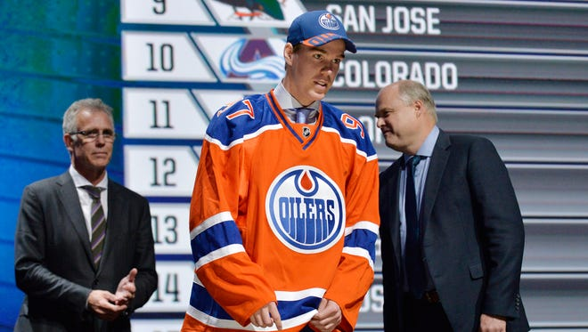 Connor McDavid walks off the stage after being taken with the No. 1 pick in the NHL draft.