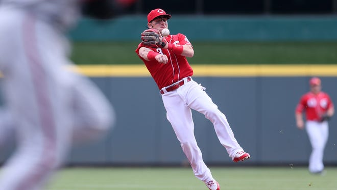 Cincinnati Reds second baseman Scooter Gennett (3) throws to first base for an out in the second inning during the National League baseball game between the Washington Nationals and the Cincinnati Reds, Saturday, March 31, 2018, at Great American Ball Park in Cincinnati.