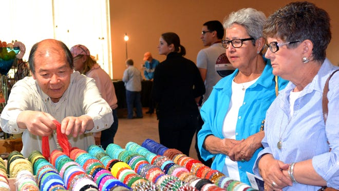 Gloria Dorsett, middle, and Stephanie O'Dell, right, listen to Park Pang of Tucson, Arizona, as he shows them his hundreds of different necklaces during the fourth annual Gem & Mineral Show at the Farm & Ranch Museum.
