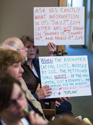 Bob Davis (left) and Diane Derrick of Hinesburg hold up signs as Eileen Simollardes of Vermont Gas Systems (not pictured) testifies before the Public Service Board in Montpelier on Wednesday, March 25, 2015. The PSB is considering whether to sanction Vermont Gas for a delay in notifying the board of an increase in the estimated construction costs of a proposed gas pipeline through Addison County. Davis and Derrick are landowners who are opposed to the pipeline crossing wetlands on their property.
