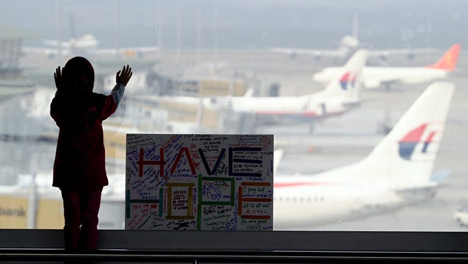 A girl stands next to a sign board made and written by the public at Kuala Lumpur International Airport on Monday.