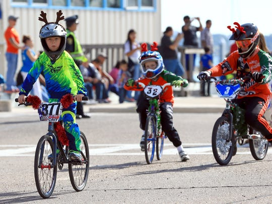 Members of the STX BMX Raceways ride their bikes during the Harbor Lights Festival Children's Parade on Saturday, Dec. 5, 2015, in Corpus Christi.