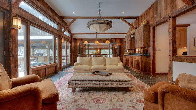 The interior of the great room is clad in old barn siding. The 3,000-square-foot house sits on 4 acres at the confluence of Swallow and Sparkle lakes.
