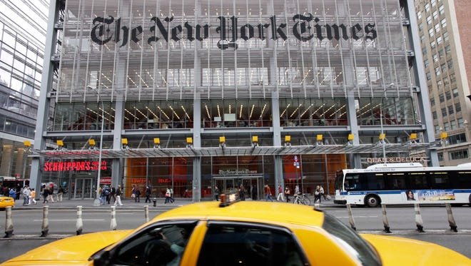 Traffic passes The New York Times building, in New York on Oct. 18, 2011. The newspaper on May 31, 2017, began offering buyouts to editorial staffers, seeking to reduce the number of editors on staff.