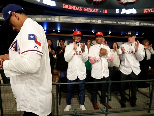 Bubba Thompson, left, an outfielder from McGill-Toolen Catholic High School in Mobile, Ala., adjusts a jersey as draftees, from left, Jordon Adell, Hunter Greene, and Trevor Rogers applaud after Thompson was selected No. 26 by the Texas Rangers in the first round of the Major League Baseball draft, Monday, June 12, 2017, in Secaucus, N.J. (AP Photo/Julio Cortez)