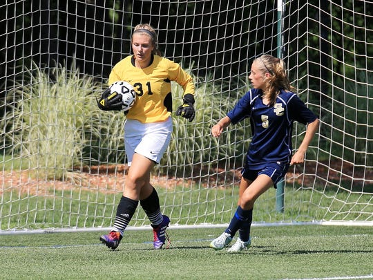 Retrieving the ball for the Chiefs is senior goalkeeper Jordan Anheuser. At right for the Cougars is Meghan Solek.
