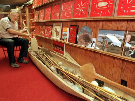In 1998, Don Miller sits amid some of his collectibles in the basement of his rural Waldron, Ind., property and demonstrates how to use a paddle that goes with the dugout canoe from South America seen in the foreground. Arrowheads and other items are in frames along the wall.