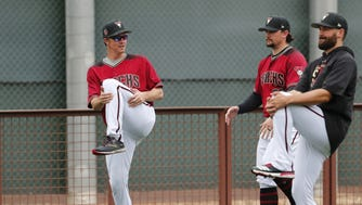 Diamondbacks starting pitcher Zack Greinke (left) warms up during the first day of workouts for pitchers and catchers on Wednesday.