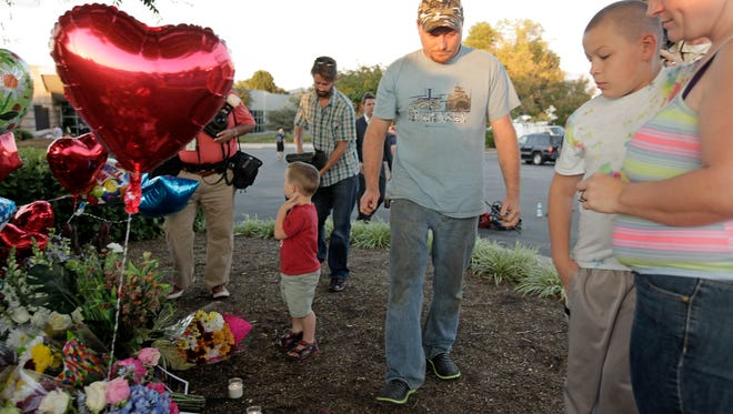 ROANOKE, VA - AUGUST 26: Jason and Patricia Grice and their sons Matthew Fajardo, 11, and William , 3, (background) bring flowers and candles to a memorial for the two journalists that were killed this morning during a live broadcast on August 26, 2015 in Roanoke, Virginia.
