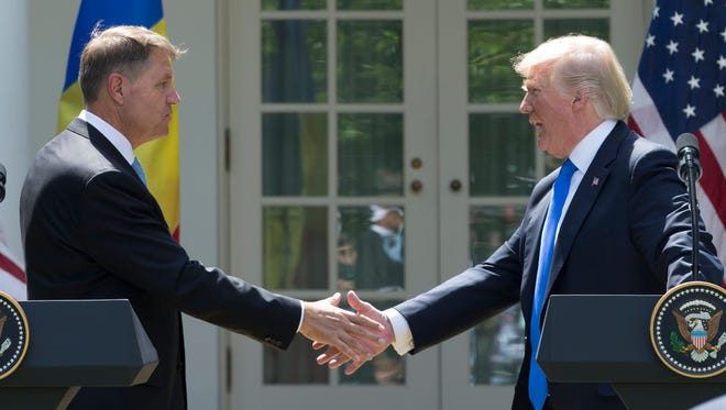 President Trump and President of Romania Klaus Iohannis shake hands during a joint news conference in the Rose Garden of the White House Friday.