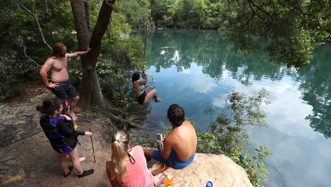 Savannah McNamer swings out in to the CherokeeSink while her boyfriend, left, Nick Acrivos, children Rizzo, 8, and Juno, 6, Jesse Register and Sendal Stewart watch from the springs's edge on a warm Wednesday afternoon at the Wakulla watering hole.
