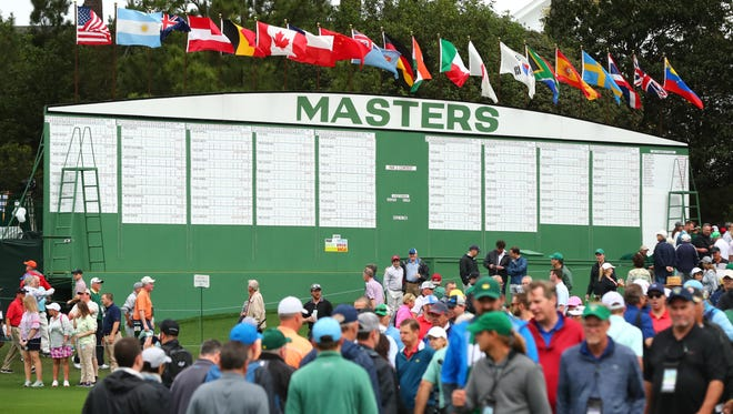 Patrons make their way in front of the main leaderboard during a practice round Wednesday.