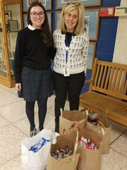 Caroline DiGrande, a junior at Mount Saint Mary Academy and a resident of Warren, poses with Midge Johnson, moderator for the Buddy to Buddy Club at Warren Middle School where the candy donations were packaged and sent to Metro World Child.
