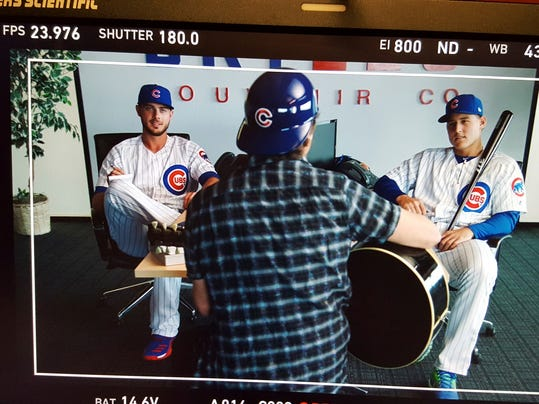 This image provided by Major League Baseball shows Chicago Cubs baseball player Kris Bryant, left, Pearl Jam lead singer Eddie Vedder, center, and Cubs' Anthony Rizzo, while shooting a commercial for the mock Bryzzo Souvenir Company in Mesa, Ariz., Wednesday, February, 22 2017. Bryant and Rizzo had a big hit with their Bryzzo Souvenir Company commercials last season and are stepping up their game for this year's spots. (MLB via AP)