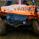 """Greg Manley competes in the Pike County Demolition Derby Saturday, July 2, 2016 at the Pike County Fairgrounds. Manley's car is decorated with """"Rhoden Proud, Rhoden Strong."""" Dana Rhoden was one of eight people killed on April 22, 2016 in Pike County. She was Greg's aunt."""