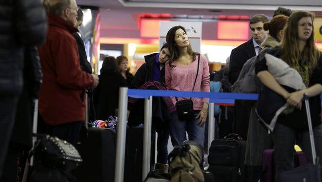 Karen Barker, center right, and her daughter, Grace Barker, 13, wait in line to see if they will be able to board a rescheduled flight to Texas at LaGuardia Airport on Jan. 26, 2015.