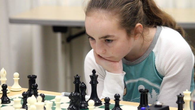 Sophia Moore, 12, studies the chessboard during the second round on Saturday. Moore, a Las Cruces resident and the New Mexico Girls Champion, went on to beat her opponent in this game.