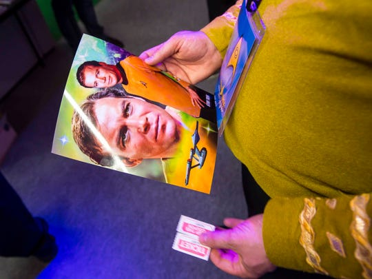 A fan holds a picture of Captain James T. Kirk at Star