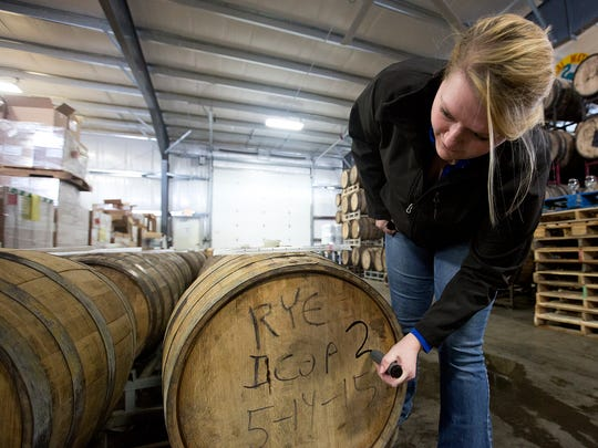 Lab technician Haley Meyer, left,  marks a rye barrel that holds an imperial chocolate oatmeal porter. Getting new bourbon barrel beers to market can take years of experimenting and testing.