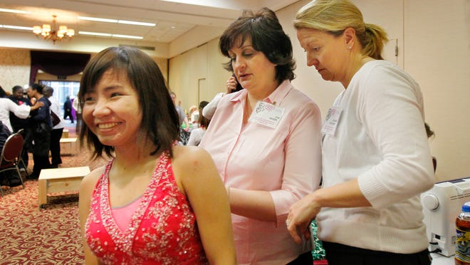 Wilson Magnet student Mary Lee of Rochester, left, is all smiles as Sue Geiger of Fairport, center, and Colleen Spiegelhoff of Victor, help with alterations on a dress she picked out at the Prom Fair.