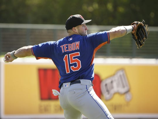 Tim Tebow warms up before his fall league debut on