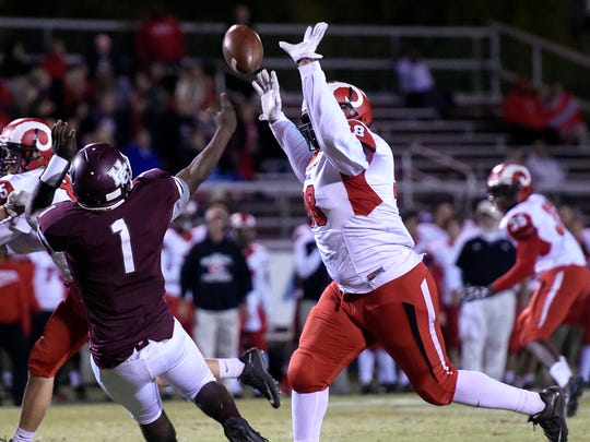 Henderson County quarterback Skip Patterson releases a pass before getting hit by Sean Cleasant of DuPont Manual during the second quarter of the game at Colonel Stadium in Henderson Friday.