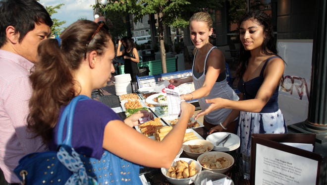 Kat Akridge, right, and Vita Yegorova serve guests outside Formosa during Taste of Iowa City on Wednesday, Aug. 28, 2013.