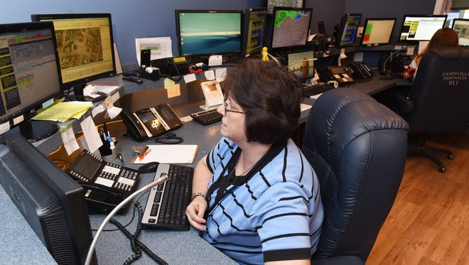 Karen Schroeder, a dispatcher for the Zanesville Police Department for 24 years, answers a call at the city's dispatch center.
