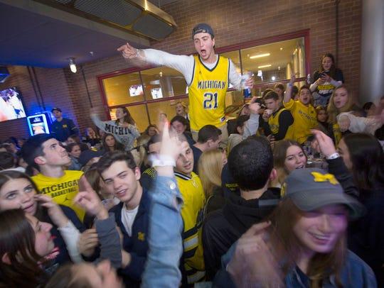 "Fans scream ""Go Blue"" at the Garage Bar in Ann Arbor"