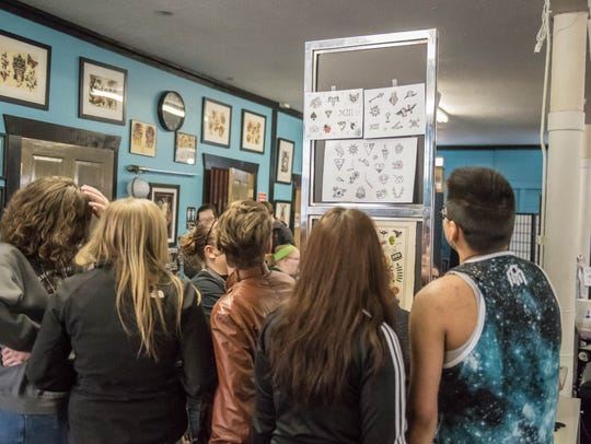 Customers check out the designs available for the $31 special at Cereal City Tattoo & Piercing on Friday, April 13.