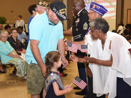 Pat Mason-Guillory hands out American Flags to veterans during Memorial Day ceremonies in Opelousas.