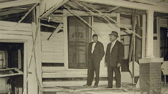 Martin Luther King Jr. inspects the damage done to his Montgomery, Alabama, home by a Jan. 30, 1956, bombing.