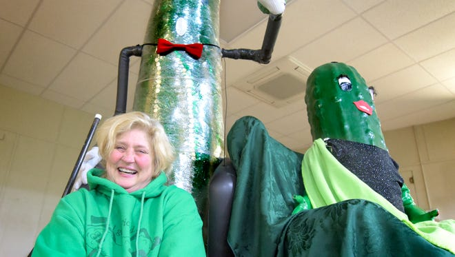 Dillsburg Area Pickle Committee member Deana Weaver poses with the Pickle family -- Mr. and Mrs. Pickle and Lil' Dill, top, at the Citizen's Hose Fire Co. on Tuesday, Dec. 29, 2015. During the New Year's Eve Pickle Drop, Lil' Dill stars in the Baby Pickle Drop at 7 p.m. and Mr. Pickle takes the plunge at midnight. The committee is in charge of the New Year's festivities and the PickleFest celebration in May. (Bill Kalina - The York Dispatch)