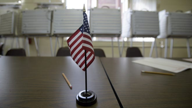 An American flag sits on the table top in front of the voting booths at a polling station in this file photo.