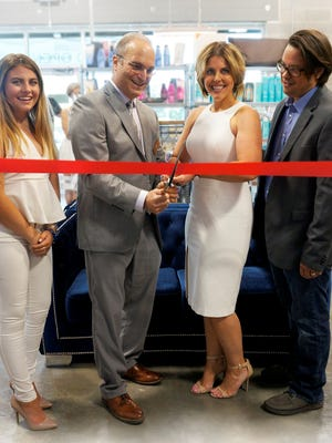 Parlour 7 Salon owner Melissa Sullivan got some help cutting the ribbon on Parlour 7 from Northville Mayor Ken Roth, her daughter Mattison (left) and husband Erik (right).