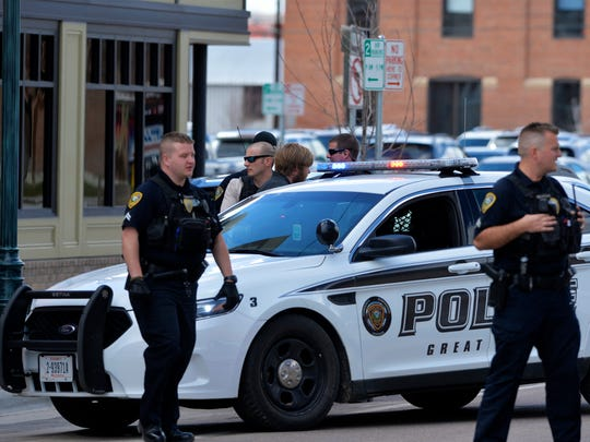 Great Falls Police take a person of interest into custody in front of Hoglund's Western Wear on 1st Avenue South on Tuesday afternoon. At the time police were searching for man who robbed the Stockman Bank on 1st Avenue North earlier in the afternoon.