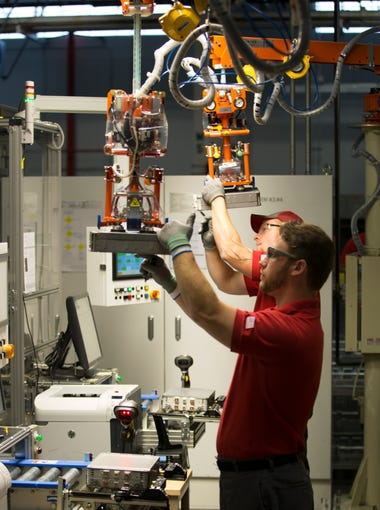 Workers check assembled battery modules during the quality assurance process.