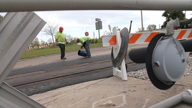 Road workers put the finishing touches on the Ashland Railway crossings on Ohio Route 13 north of downtown on Thursday. Railway officials said that the route should be open for traffic by Friday morning.