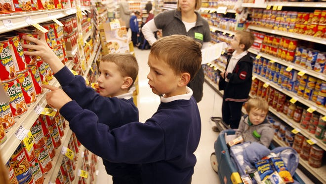 Thomas McCoy (left) and Ben Sweeten, students at Blessed Sacrament School select canned goods to buy at the Fort Mitchell Remke Market. This location was the fourth Remke to close since 2015.