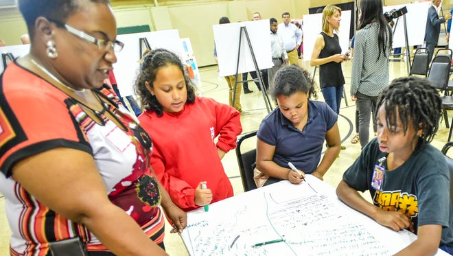 Erica Williams with New Vision Leadership works with students, Zarie Shelvin, Jakyli Evans, Amile George to develop suggestions. The general public was invited to view the  11 refinements proposed for the I-49 corridor project and meet with project consultants to discuss their concerns.April 27, 2016.
