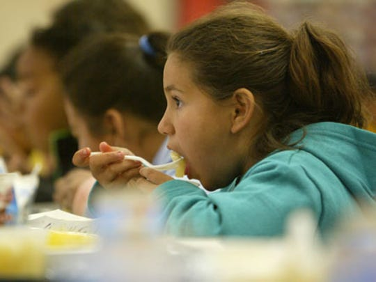 An elementary school student enjoys her lunch.