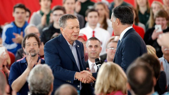 John Kasich shakes hands with Mitt Romney during a