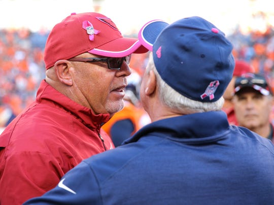 Head coach Bruce Arians of the Arizona Cardinals and head coach John Fox of the Denver Broncos shake hands after the game in Denver on Oct. , 2014.