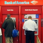 Customers use ATM machines at a Bank of America branch office in Boston.